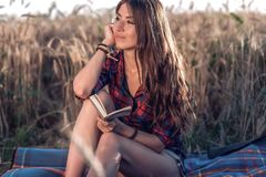 Beautiful brunette girl in the field, shirt shorts. Concept new ideas, dreams and fantasies. Happy in fresh summer in. Beautiful brunette girl in the field stock photo