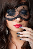 Beautiful brunette girl with fine art lacy manicur. Closeup portrait of attractive young brunette girl with long dark ringlets and fine art manicure wearing lacy royalty free stock image