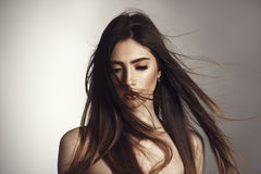 Beautiful brunette girl with fluttering hair on wind. Glamour vogue style photoshoot royalty free stock images