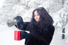 Beautiful brunette girl in a fur coat on background of a winter forest, pours hot coffee from the Turks in the red Cup royalty free stock photography