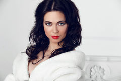 Beautiful Brunette Girl in fur coat over modern interior  Stock Photos