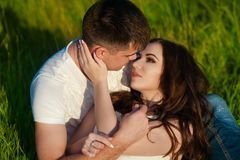 Beautiful brunette girl and guy lying in grass and holding tightly hands. The concept of tenderness and affection Royalty Free Stock Images