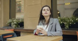 Having a Cup of Coffee. Beautiful brunette girl having cup of coffee sitting in cozy outdoors cafe stock footage