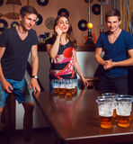Beautiful brunette girl having fun with twins playing beer pong Stock Image