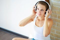 Beautiful brunette girl with headphones listening to music while sitting on the floor in an empty room on the white wall royalty free stock image