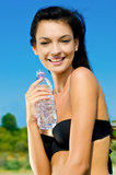 Beautiful brunette girl holding a bottle of water. Stock Photo