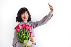 Beautiful brunette girl holding bouquet of tulips and gift box and taking selfie on white background indoors, space for text. Stylish young woman with flowers stock images