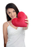 Beautiful brunette girl holding in front a red heart. Happy woman, Valentine day. Royalty Free Stock Images