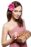 Brunette girl holding gift box. Beautiful brunette girl holding gift box and looking at camera Stock Photo
