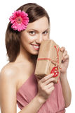 Brunette girl holding gift box. Beautiful brunette girl holding gift box next to her face and smiling, looking at camera Stock Photos