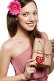 Brunette girl holding gift box. Beautiful brunette girl holding gift box and smiling, looking at camera Stock Photo