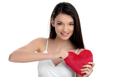 Beautiful brunette girl holding a red heart. Heart broken, loveless, angry on love. Woman tearing up a heart. Valentine day. Stock Photos
