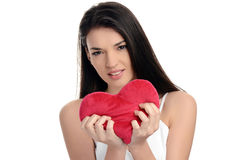 Beautiful brunette girl holding a red heart. Heart broken, loveless, angry on love. Woman tearing up a heart. Valentine day. Stock Photo