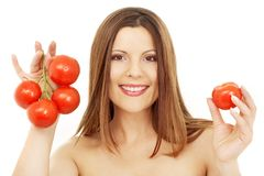 Beautiful brunette girl holding tomatos Royalty Free Stock Photos
