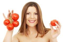 Beautiful brunette girl holding tomatos. Over white Royalty Free Stock Photos