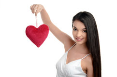 Beautiful brunette girl holding up a red heart. Happy woman, Valentine day. Stock Photo