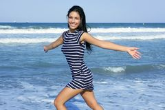 Beautiful brunette girl jumping on the beach Stock Photos