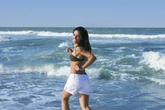 Beautiful brunette girl jumping on the beach Royalty Free Stock Photography