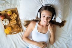 Beautiful brunette girl listening to music on headphones in bed . Breakfast Woman in the morning royalty free stock photo