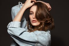 Beautiful brunette girl with long flowing hair dressed in jeans jacket poses holding her hands on her head on the dark stock photography