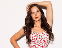 Beautiful brunette girl with long hair and blue eyes posing in bright summer short dress nex to white background. Close up. Indoor Royalty Free Stock Photo