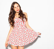 Beautiful brunette girl with long hair and blue eyes posing in summer short dress on a white background. Indoor Royalty Free Stock Photo