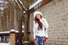 Beautiful brunette girl with long hair in fur vest and bright ma royalty free stock photography