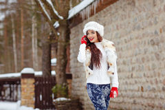 Beautiful brunette girl with long hair in fur vest and hat cheer Stock Photo