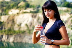 Beautiful brunette girl with long hair holding a bottle of water Royalty Free Stock Photo