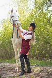 Beautiful brunette girl with long hair posing with a red horse in forest. Autumn landscape, beautiful brunette girl with long hair posing with a red horse in the Stock Photography