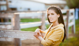 Beautiful brunette girl with long hair smiling near an old wooden fence.  Stock Photo