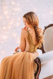 Beautiful brunette girl. The brunette girl in a luxurious dress. Background white room. Film colors royalty free stock images