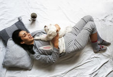 Beautiful brunette girl lying and cuddling her cute dog on bed and smiling Stock Photo