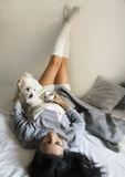 Beautiful brunette girl lying with her cute dog on bed with legs up. Beautiful brunette girl lying with her cute white maltese dog on bed with legs up Stock Image