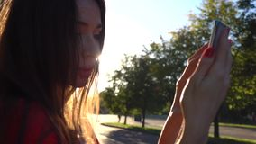 Beautiful brunette girl making selfie in the park, warm sunset colors. Slow motion video stock footage