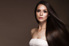 Beautiful brunette girl in move with a perfectly smooth hair, and classic make-up. Beauty face. royalty free stock photography