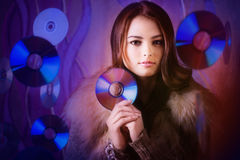 Beautiful brunette girl with multiple shiny cds Royalty Free Stock Photography