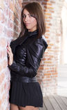 Beautiful brunette girl near a retro brick wall Royalty Free Stock Photos