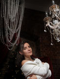 Beautiful brunette girl  next to a crystal chandelier Stock Image