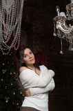 Beautiful brunette girl  next to a crystal chandelier Royalty Free Stock Photo