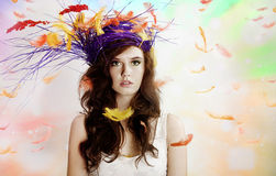 Beautiful brunette girl over feathers. Stock Image