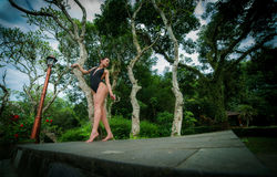 Beautiful brunette girl with perfect body in swimsuit in park on the Bali. Beautiful brunette woman with perfect body in swimsuit in the Bali. Indonesia Stock Photography