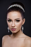 Beautiful brunette girl with perfect skin, evening make-up, wedding hairstyle and accessories. Beauty face. Stock Photo