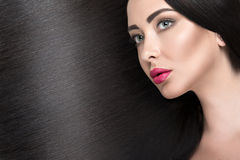 Beautiful brunette girl with a perfectly smooth hair and classic make-up. Beauty face. Stock Photo