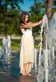 Beautiful brunette girl playing at  water fountain Royalty Free Stock Images