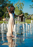 Beautiful brunette girl playing at  water fountain Stock Image