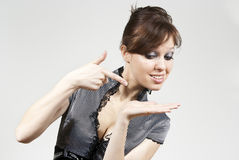 Beautiful brunette girl points the finger. At the hand Stock Photography