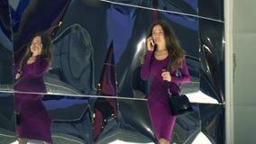 Beautiful brunette girl in purple dress walking and talking on her mobile phone. 4K video stock video
