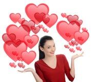 Beautiful brunette girl raising her hand presenting. Valentine day. Stock Photo