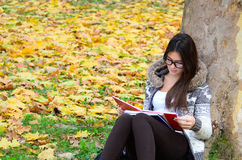 Beautiful brunette girl reading book in nature Stock Photo